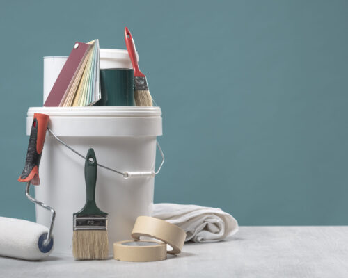 Painter and decorator work table, color swatches, painting roller and paint brushes, copy space
